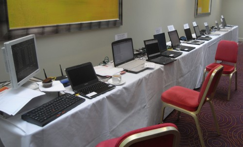Table with server, router and laptops with exercise cards stuck on top